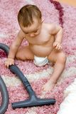 Cute caucasian baby with vacuum cleaner Stock Images