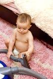 Cute caucasian baby with vacuum cleaner Stock Photos