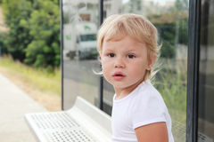 Cute Caucasian blond baby girl on a bus stop Royalty Free Stock Image