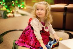 Cute Caucasian blond curly hair girl is playing with train toys indoor on the lights blur background. Girl is happy and smiling royalty free stock photos