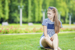 Cute Caucasian Blond Teenage Girl With Longboard in Green Summer Park Stock Images