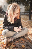 Cute Caucasian blond teenage girl with smart phone Royalty Free Stock Images