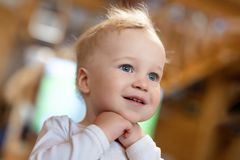Cute caucasian blond toddler boy pleasantly surprised looking somewhere indoors. Adorable little child holding hands under chin royalty free stock photography