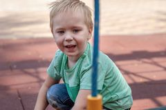 Cute caucasian blonde baby boy with blue eyes sits on the cover of children playground. Funny look, alone. Casual jeans, aquamarine shirt. Outdoors, sunny day royalty free stock image