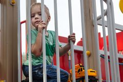 Cute caucasian blonde baby boy sits under the fence of children playground. Cute, serious and humile expression on the face, stron stock photography