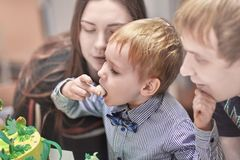 Cute caucasian blonde boy eats sweeties from the Birthday cake sitting between the parents. stock photos