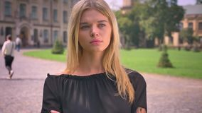 Cute caucasian blonde woman is standing and looking at camera with serious face outside, near park.  stock video footage