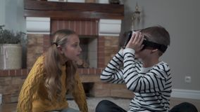 Cute Caucasian boy in VR glasses talking to the pretty girl and looking around. Brother and sister playing with new stock video