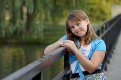 Cute caucasian brunette girl leaning on railing Stock Image