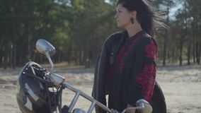 Cute caucasian brunette girl standing at the motorcycle looking away in front of pine forest. Hobby, traveling and. The girl with black hair standing at the stock video