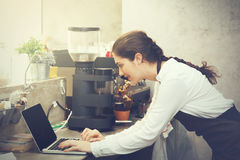 Cute Caucasian busy working with laptop on coffee shop counter stock photos