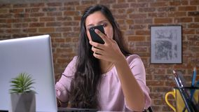 Cute caucasian casual girl is working on laptop and dis distracted with phone call, relaxed confident face, sitting at. Desktop near brick wall stock video