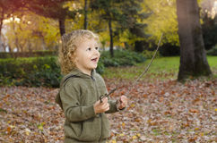 Cute Caucasian child playing in park with sticks Stock Photo