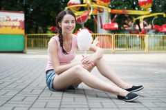 Cute caucasian girl in amusement park is eating pink candyfloss. Portrait of happy attractive young woman with cotton candy. Royalty Free Stock Photo