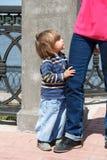 Cute Caucasian girl embrace mother leg royalty free stock photos