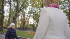 Cute caucasian girl in white hat and warm blue coat spending autumn day with her grandmother in the park. Mature woman. In beige cloche hat and white coat stock video