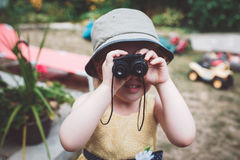Cute Caucasian girl in yellow dress and hat  looking through binoculars Stock Images