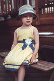cute Caucasian girl in yellow dress and hat outside on house backyard on summer day Royalty Free Stock Photos