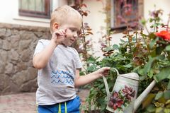 Cute baby boy waters the flowers on the back yard, mother assistant. Cute caucasian little boy with blonde hair and blue eyes watering plants roses in the yard royalty free stock images