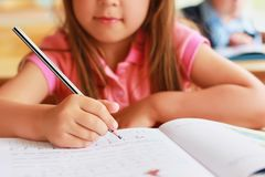 A sweet Caucasian child in school at a desk writes in a notebook. A cute caucasian little girl with long hair in a pink dress sits in a school class at a desk Royalty Free Stock Image