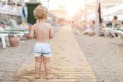 Cute caucasian toodler boy walking alone on sandy beach between chaise-lounge. Adorable happy child having fun playing at seaside stock photos
