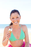 Cute caucasian woman eating ice cream on the beach Stock Images