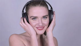 Cute caucasian woman with headphones listening music, slow motion. stock video