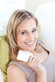 Cute caucasian woman holding a card on the sofa Royalty Free Stock Image