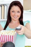 Cute caucasian woman holding a remote and popcorn Royalty Free Stock Image