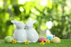 Cute ceramic Easter bunnies and dyed eggs on green grass against blurred background. Space for text stock photo
