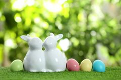 Cute ceramic Easter bunnies and dyed eggs on green grass against blurred background. Space for text royalty free stock photo