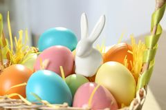 Cute ceramic Easter bunny and dyed eggs in wicker basket on table. Closeup stock images