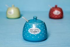 Cute Ceramic Storage Jars with Dots on Blue. Wooden background stock photo