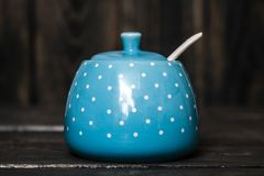 Cute Ceramic Storage Jars with Dots on Blue. Wooden background stock images