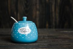 Cute Ceramic Storage Jars with Dots on Blue. Wooden background royalty free stock image