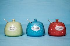 Cute Ceramic Storage Jars with Dots on Blue. Wooden background stock image
