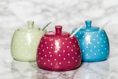 Cute Ceramic Storage Jars with Dots on White. Marble background stock photos
