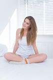Cute charismatic young woman sitting on her bed Stock Photography