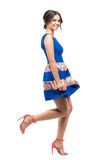 Cute charming girl in blue floral summer short dress bowing and smiling at camera. Royalty Free Stock Images