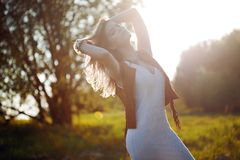 Cute charming girl in summer in the field. Young woman is happy and feels free outdoors Royalty Free Stock Photo