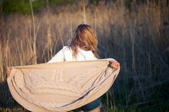 Cute charming girl in summer in the field. Young woman is happy and feels free outdoors. Back view Royalty Free Stock Photo