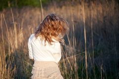 Cute charming girl in summer in the field. Young woman is happy and feels free outdoors. Back view Stock Image