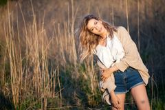 Cute charming girl in summer in the field. Young woman is happy and feels free outdoors Stock Image