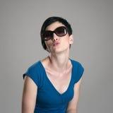 Cute charming short hair woman wearing sunglasses blowing air kiss at camera Royalty Free Stock Photos