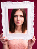 Cute charming woman looking at camera trough frame. Cute charming woman looking at camera through frame over pink background Stock Photo