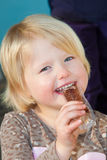 Cute cheeky little blond girl eating a sweet Stock Image