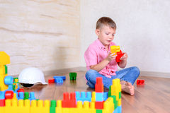 Cute cheeky young boy playing with building blocks Royalty Free Stock Images