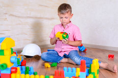 Cute cheeky young boy playing with building blocks Royalty Free Stock Photo