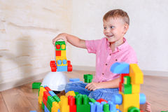 Cute cheeky young boy playing with building blocks Royalty Free Stock Image