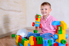Cute cheeky young boy playing with building blocks Stock Photos